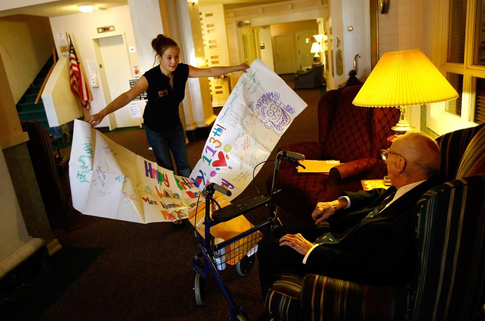 12) Николь Скотт открывает плакат, который Уолтеру Бреунингу прислали ее соученики, за два дня до празднования 113-го дня рождения Уолтера в доме престарелых в Грейт-Фоллс, штат Монтана. (Getty Images/John Moore)