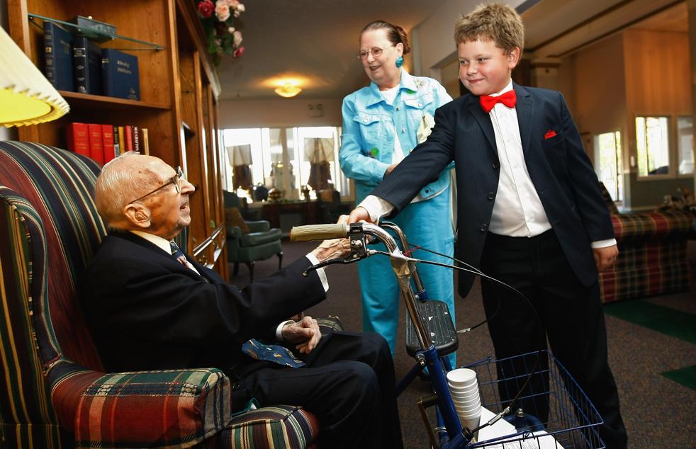 16) Уолтер Бреунинг встречает 10-летнего Мэтью Никола, который приехал вместе со своей семьей в гости к долгожителю в дом престарелых «Rainbow» (Радуга) 19 сентября. (Getty Images/John Moore)