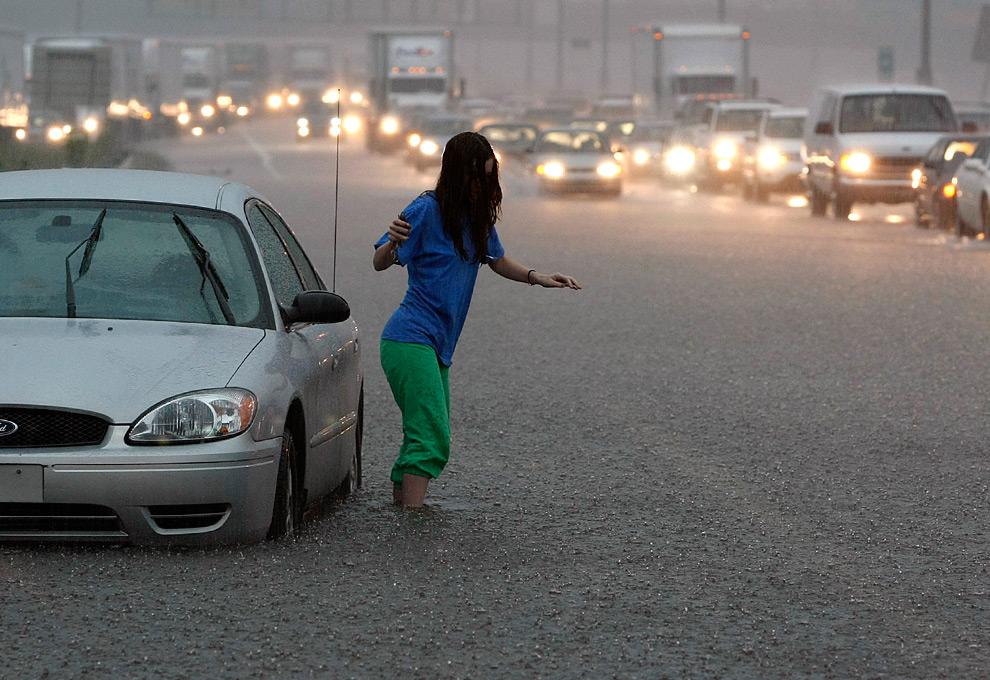 1. Девушка бросила свой затопленный автомобиль на улице I-85 South недалеко от Лилбурна, штат Джорджия, когда часть шоссе просто ушла под воду во время час-пика в понедельник 21 сентября 2009 года. (AP Photo/The Atlanta Journal & Constitution, Curtis Compton)