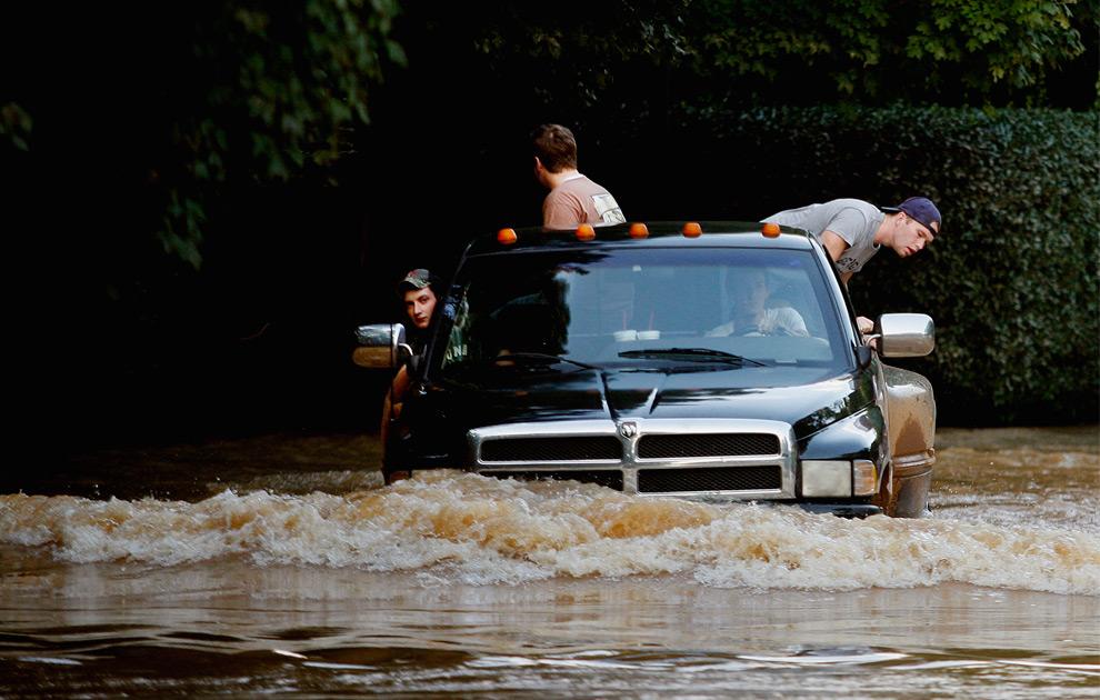 3. Жители следят за уровнем воды, выезжая по затопленной дороге из своего района, залитого водой из-за сильных ливней в Лоуренсвилле, штат Джорджия, 22 сентября 2009 года. (REUTERS/Tami Chappell)