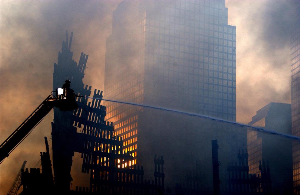 7. 19 сентября 2001 года пожарные все еще продолжали сражаться с огнем, вырывающимся из-под завалов Всемирного торгового центра. (REUTERS/PA2 Tom Sperduto/US Coast Guard)