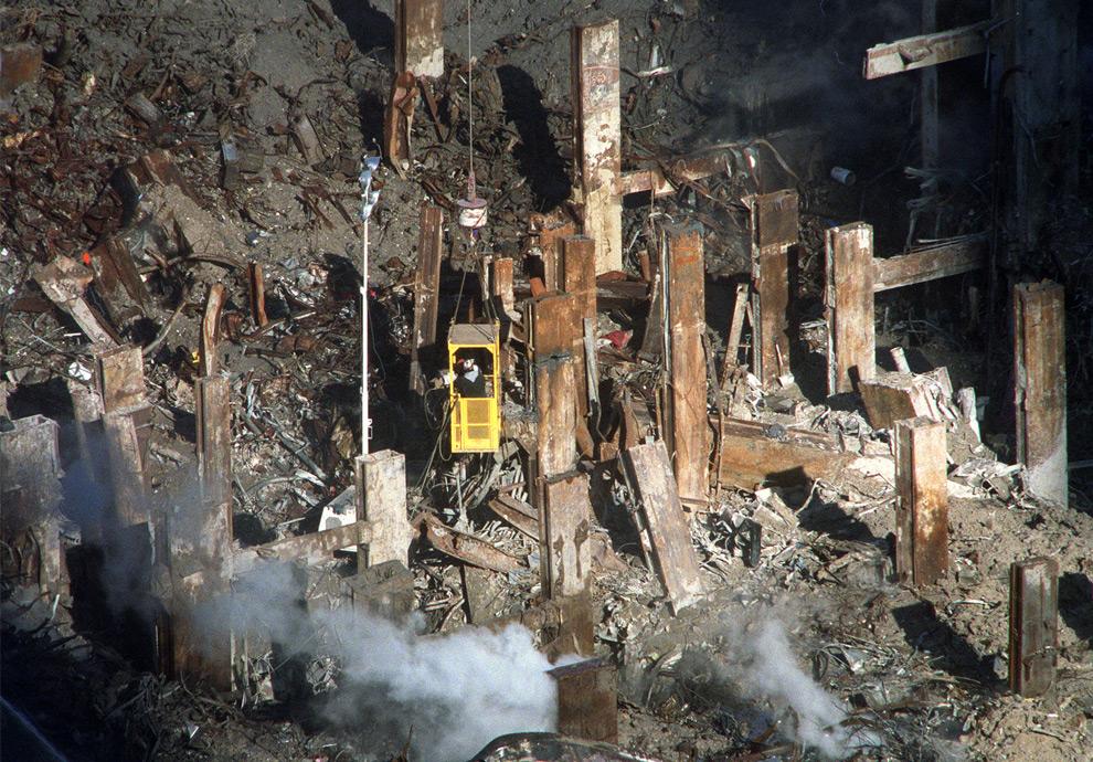8. Солнечный свет пробивается ко все еще дымящемуся месту трагедии, освещая останки второй башни и рабочих на кране, в субботу 27 октября 2001 года в Нью-Йорке. (AP Photo/William C. Lopez)