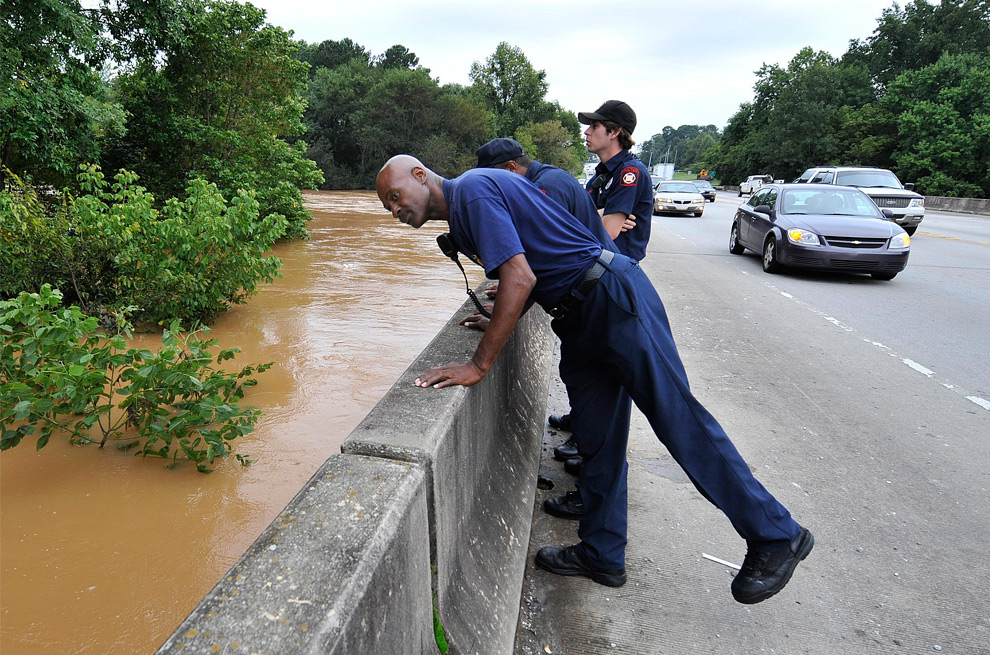 8. Пожарный округа Фултон Фред Браун смотрит через мост на улице MLK Drive на поднимающуюся реку Чаттахучи, так как поступило сообщение о попавшем в реку мужчине во вторник 22 сентября 2009 года. Мост отделает округ Кобб от округа Фултон. На мосту расстояние от воды до автомобилей составляло всего 60 см. (AP Photo/The Atlanta Journal & Constitution, Johnny Crawford)