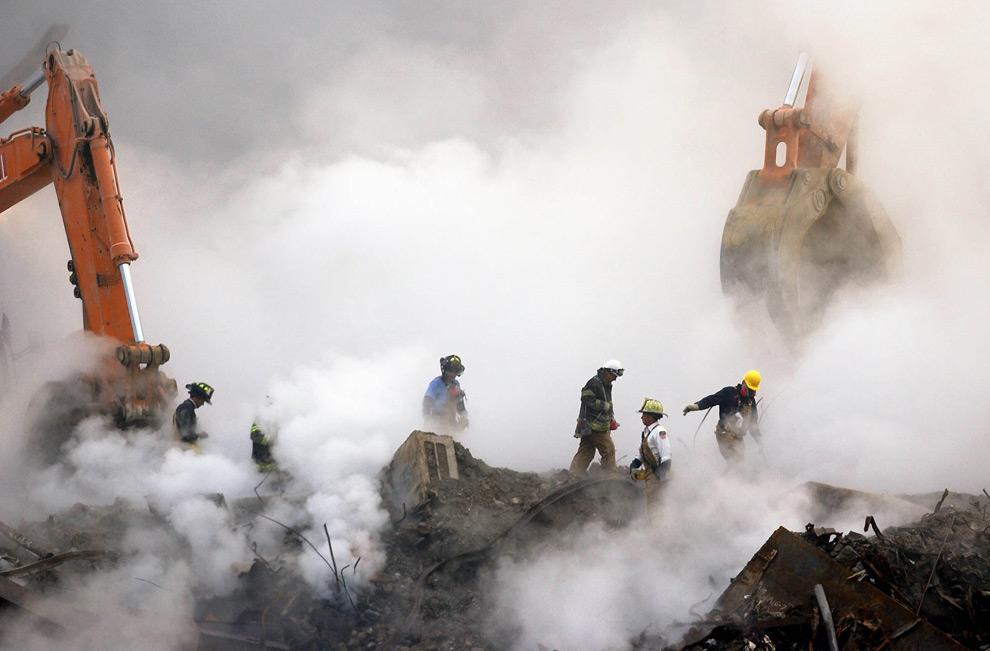 9. Пожарные прокладывают путь по руинам Всемирного торгового центра сквозь облака пыли и дыма, в четверг 11 октября 2001 года в Нью-Йорке, спустя месяц после трагедии работа на нулевой отметке все еще продолжается. (AP Photo/Stan Honda)