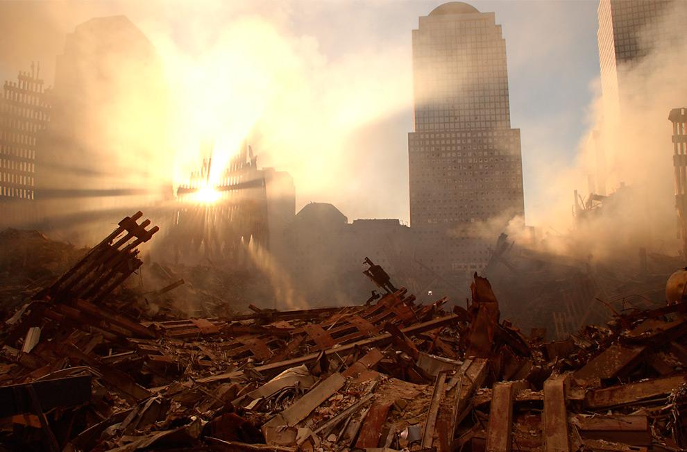 10. Солнце пробивается сквозь пыль, освещая развалины Всемирного торгового центра 15 сентября 2001 года. (Andrea Booher/FEMA News Photo)