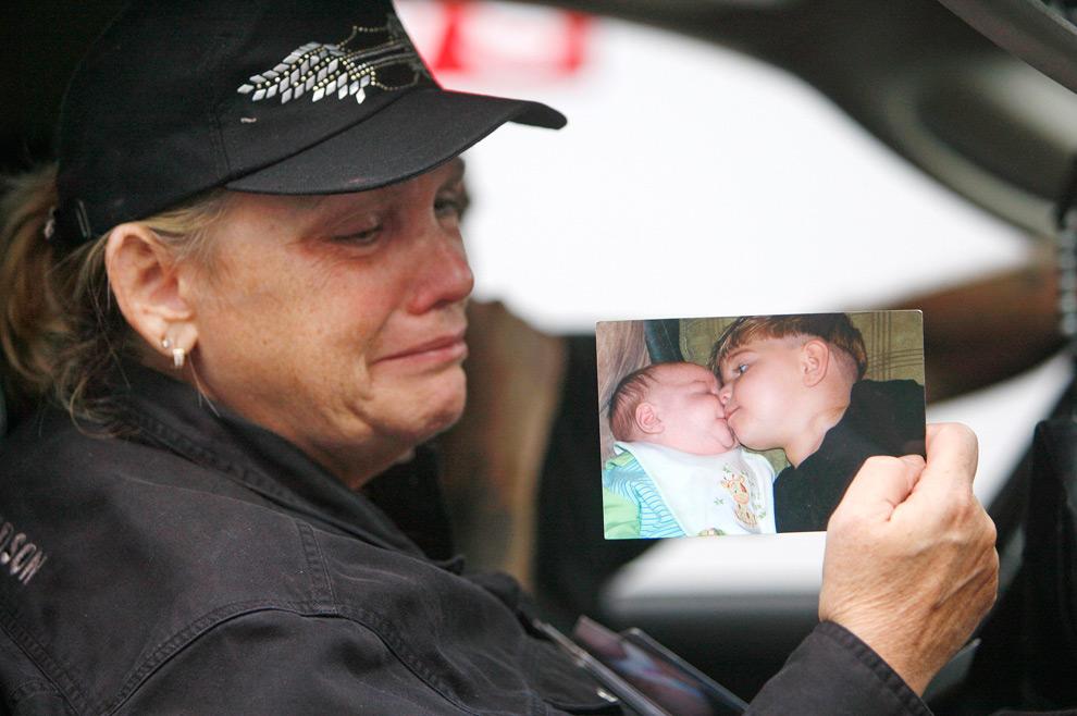 10. Пэт Кроуфорд плачет, держа фотографию своего двухлетнего внука Престона Слейда Кроуфорда (справа на фотографии), который погиб в понедельник 21 сентября 2009 года, когда его дом попросту смыло в бухте Снейк в Карроллтоне, штат Джорджия. (AP Photo/John Bazemore)