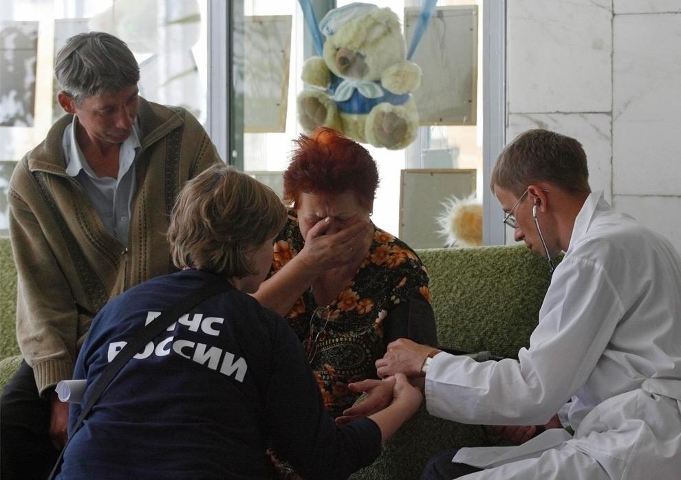 14. Медицинские работники успокаивают родственницу жертвы аварии на Саяно-Шушенской ГЭС 19 августа 2009 года. (REUTERS/Ilya Naymushin)