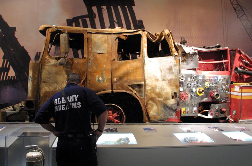 15. Пожарный из Олбани, Нью-Йорк, Брайн Ратиган смотрит на выставку экспонатов, посвященных атаке на Всемирный торговый центр, которая включает в себя пожарный автомобиль шестого пожарного отделения (на заднем фоне), в среду 4 сентября 2009 года в городском музее Нью-Йорка в Олбани. (AP Photo/Jim McKnight)