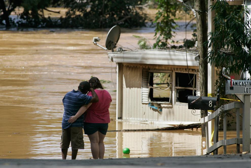 16. 19-летняя Дженнифер Бозман и Набор Торрес стоят на краю бухты Свитуотер, вышедшей из берегов и снесшей их передвижной домик во вторник 22 сентября 2009 года в Остелле, штат Джорджия. (AP Photo/John Amis)