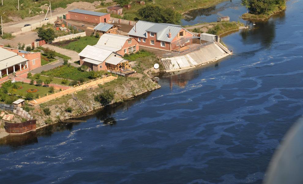 18. Здания стоят на берегу загрязненной маслом реки Енисей вниз по течению от Саяно-Шушенской ГЭС 20 августа 2009 года. В результате аварии на ГЭС в реку попало огромное количество машинного масла. (ALEXANDER NEMENOV/AFP/Getty Images)