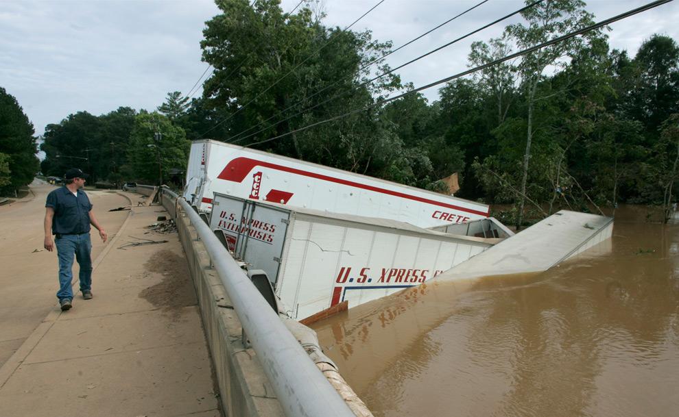 18. Прохожий оглядывается на трейлер, смытый с моста, стоящего поперек бухты Свитуотер, размытой из-за ливней. Снимок сделан в среду 23 сентября 2009 года в Остелле, штат Джорджия. (AP Photo/John Amis)
