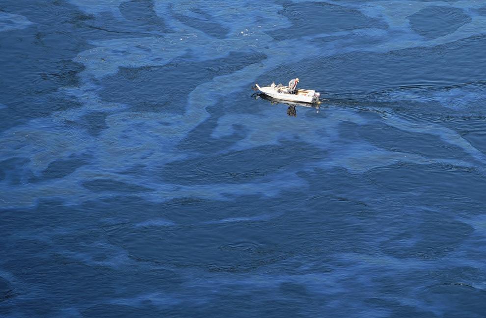 19. Мужчина плывет на моторной лодке по загрязненному маслом Енисею недалеко от Саяно-Шушенской ГЭС 20 августа 2009 года. (ALEXANDER NEMENOV/AFP/Getty Images)