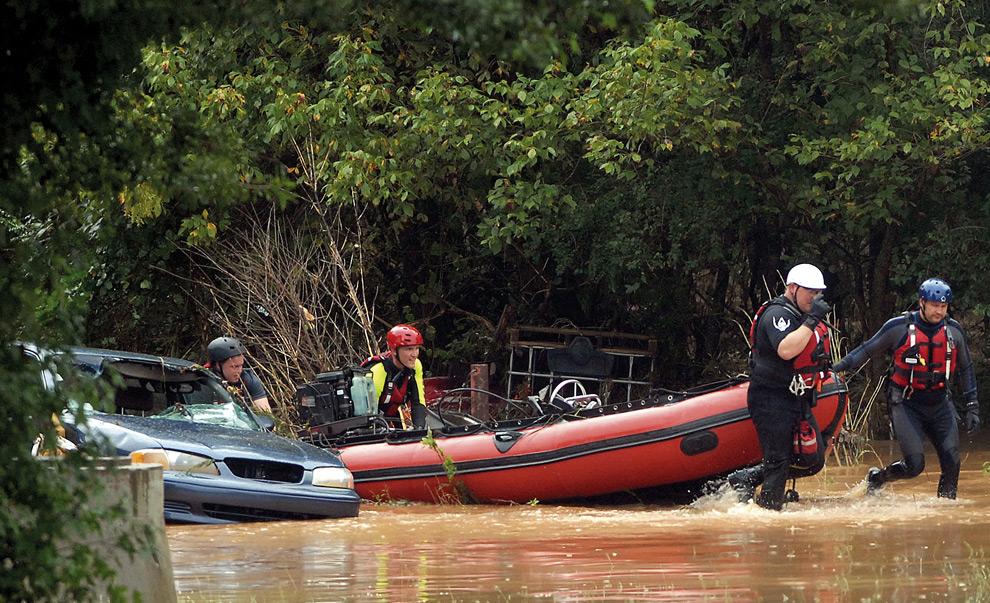 20. Команда пожарных Гвиннетт везет спасательную лодку по реке Еллоу в понедельник 21 сентября 2009 года в Лилбурне, штат Джорджия. Лодка перевернулась ранее в этот же день и была отнесена течением. Автомобиль на этом же снимке смыло с ближайшей стоянки. (AP Photo/Jason Braverman, Gwinnett Daily Post)