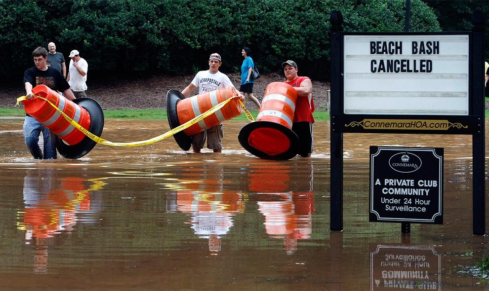 21. Слева направо: Гарретт Джейкобс, Дакота Нельсон и Леви Райт передвигают заграждения на более высокий уровень после того, как вода в реке Еллоу продолжила подниматься в понедельник 21 сентября 2009 года в Лилбурне, штат Джорджия. В районе была отменена пляжная вечеринка, запланированная на понедельник. (AP Photo/Atlanta Journal-Constitution, Curtis Compton)