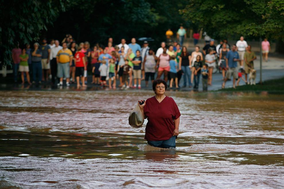 23. Раксандра Токито отважилась перейти вброд дорогу, направляясь на работу в больницу Эмори из своего района, который был отрезан из-за наводнения в Лоренсвилле, штат Джорджия, 22 сентября 2009 года. (REUTERS/Tami Chappell)