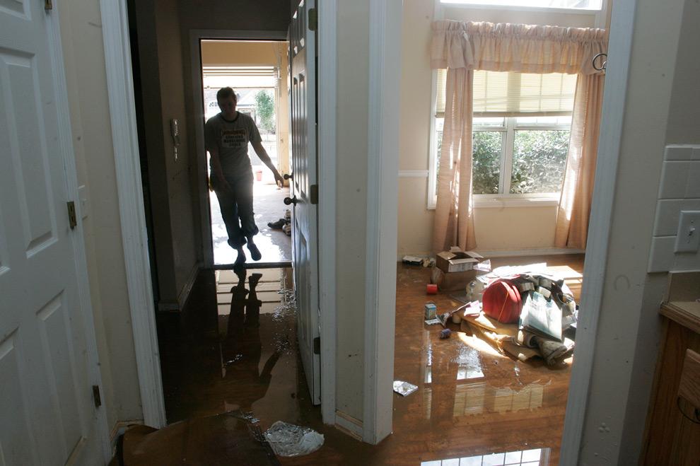 26. Доброволец Эрин Берри входит в дом, чтобы помочь убрать после наводнения в бухте Свитуотер в среду 23 сентября 2009 года в Остелле, штат Джорджия. (AP Photo/John Amis)