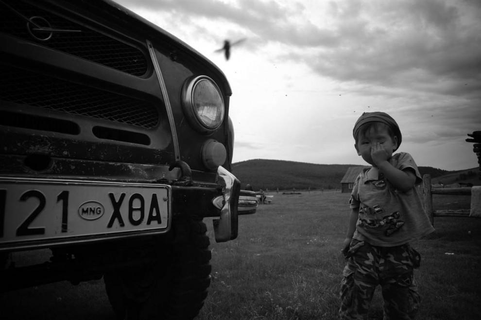 24. Маленький мальчик пытается отпугнуть мошку. Видите эти черные точки  в небе? Это мухи. В Монголии очень крупные мошки. (David Lom/NBC News)
