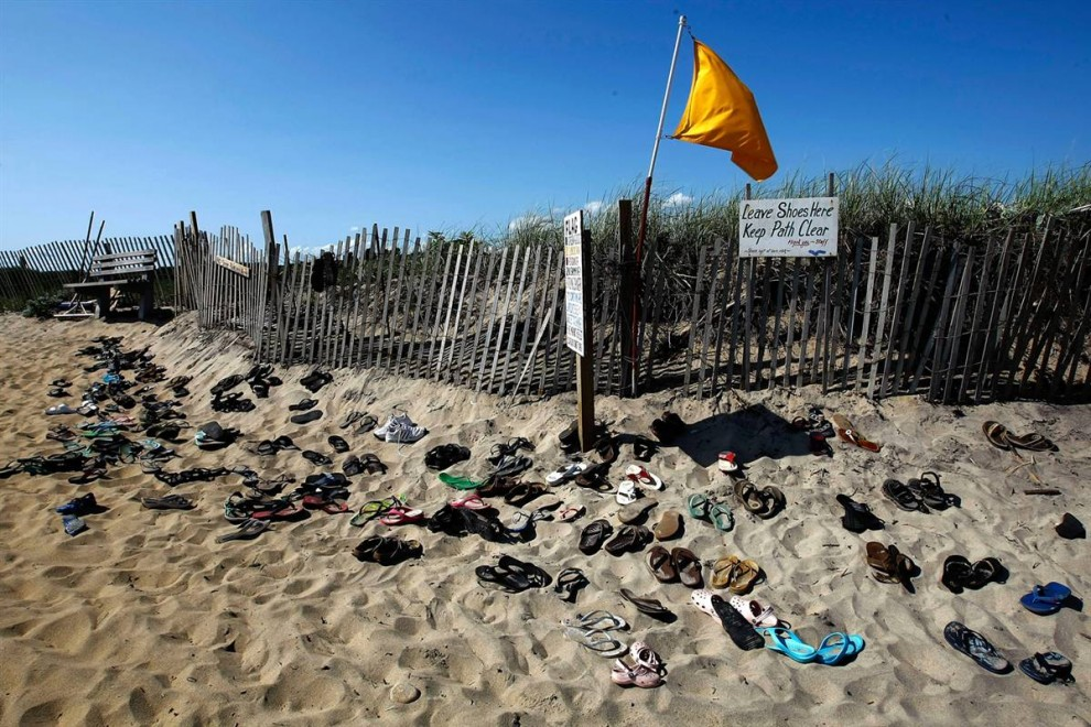 10. Обувь у входа на пляж Люси Винсент в Чилмарке, Массачусетс. Этот частный пляж могут посещать только жители Чилмарка с 1 июня по 30 сентября. Если вы планируете сюда семейный визит, будьте осторожны, так как в восточной части пляжа есть сектор, где можно загорать голышом. (Win McNamee/Getty Images)