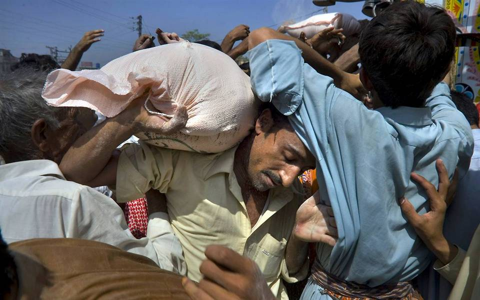 7.  Pakistan membawa sekarung tepung, dibeli dengan uang yang diterima dari Pemerintah, selama bulan suci Ramadhan, di Rawalpindi, Pakistan.  (Anjum Naveed / AP)