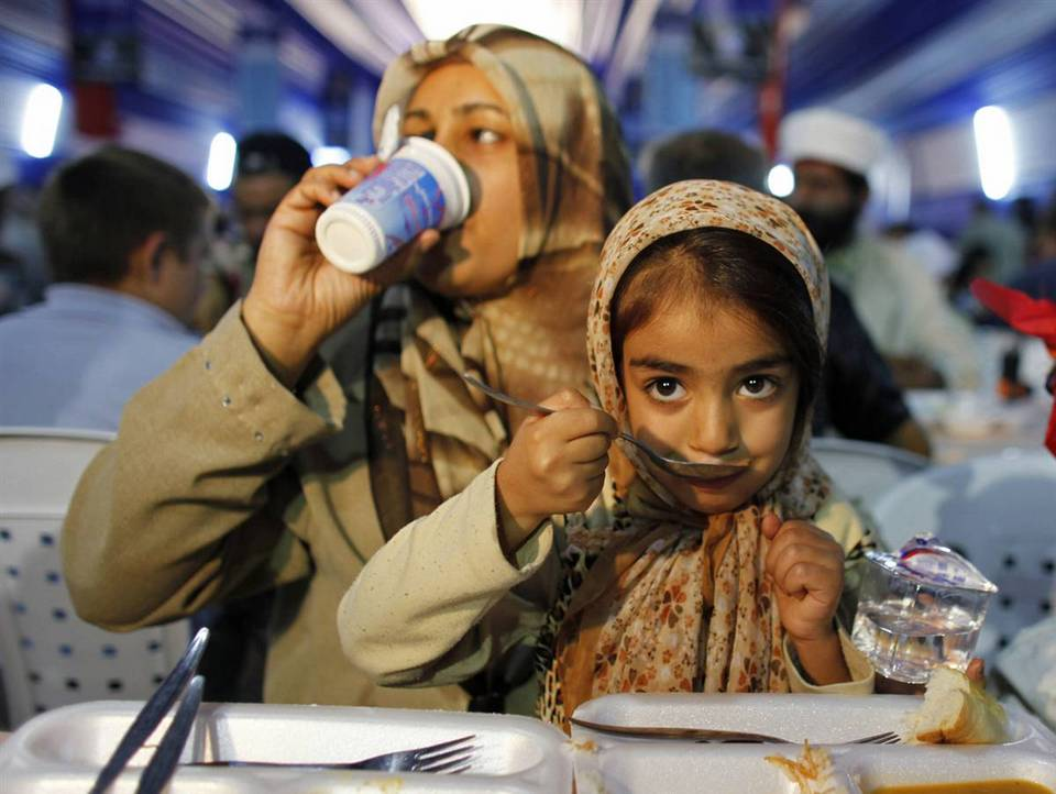 10. Мусульманские семьи разговляются в большой палатке в первый день священного месяца Рамадана в Стамбуле в пятницу. (Osman Orsal/Reuters)
