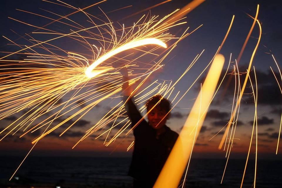 11. Палестинский мальчик забавляется с бенгальским огнем накануне мусульманского священного месяца Рамадан в Газе. (Mohammed Abed/AFP - Getty Images)