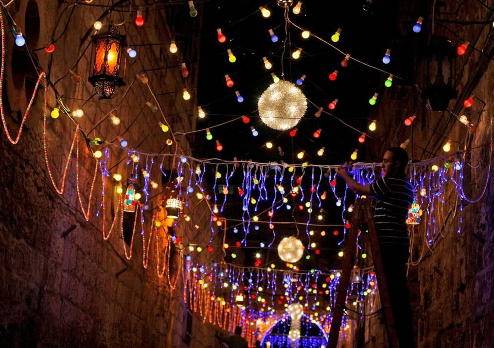 """13.  Palestina Muslim karangan bunga jalan kota tua Yerusalem untuk persiapan Ramadhan pada hari Jumat.  Bulan suci - festival, malam berjalan dengan teman-teman, serta """"iftar"""" - makan malam saat matahari terbenam untuk menandai akhir puasa.  (Muhammad Muheisen / AP)"""