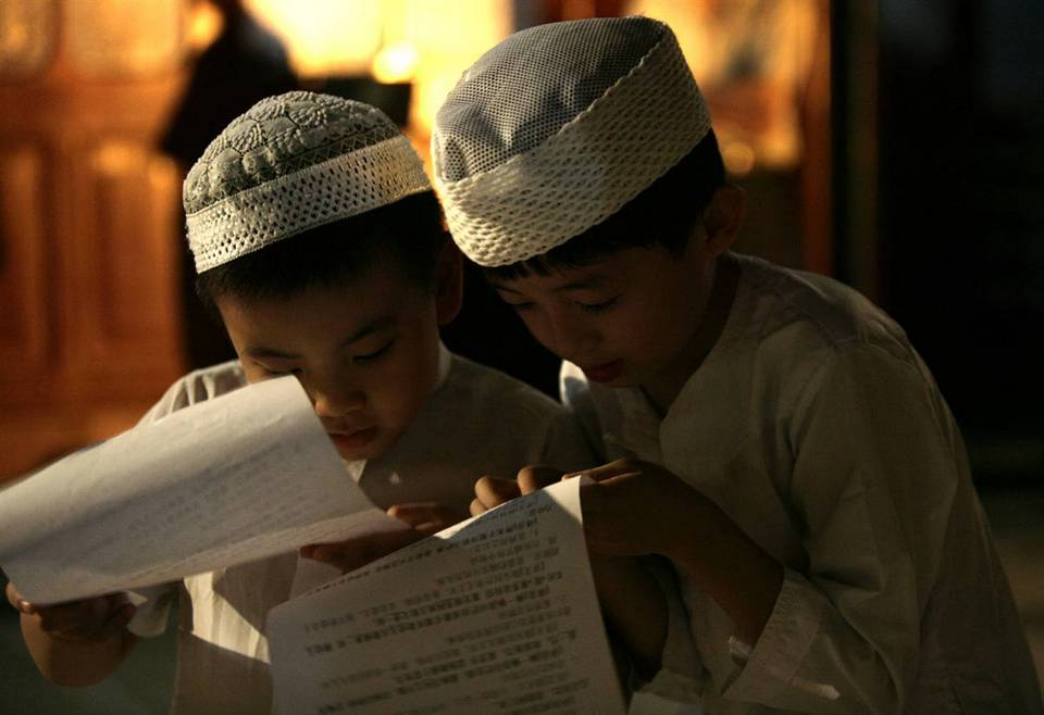 14.  Anak-anak Muslim untuk membaca sebelum shalat Jumat di sebuah masjid di Beijing.  (Grace Liang / Reuters)