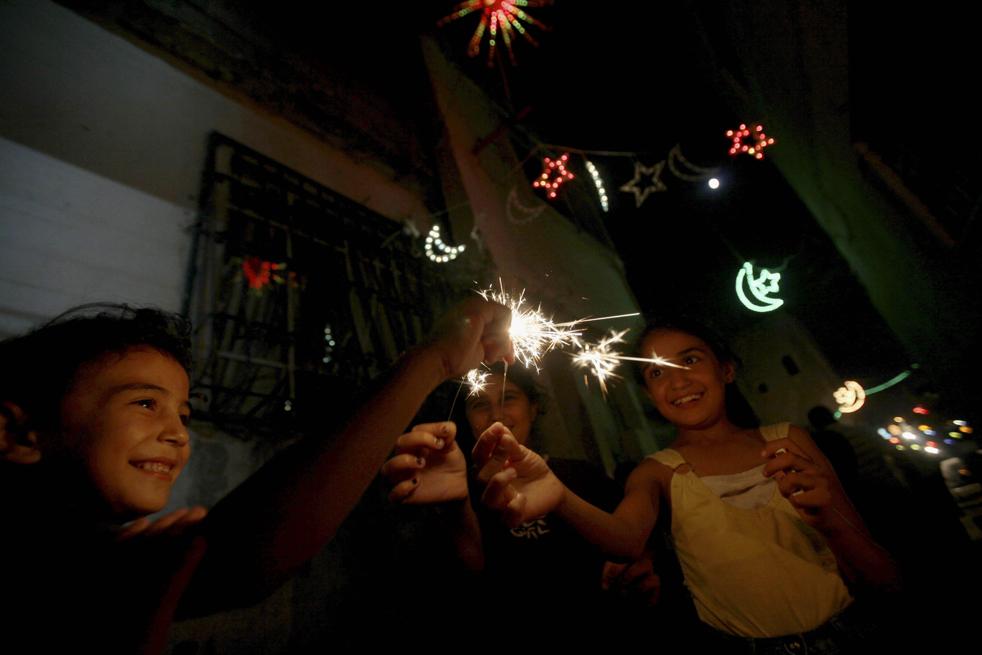 20.  Palestina gadis dengan kembang api setelah melanggar selama bulan suci Ramadhan di kamp pengungsi Tepi Barat Kalandia, antara Ramallah dan Yerusalem.  (AP / Muhammad Muheisen)