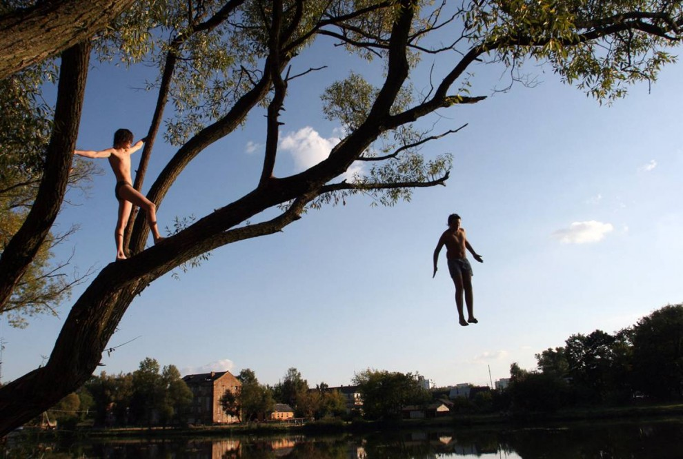 1) С этого дерева в Минске дети прыгают в воду, наслаждаясь последним летним днем перед началом учебного года. (Alexey Gromov/AFP - Getty Images)