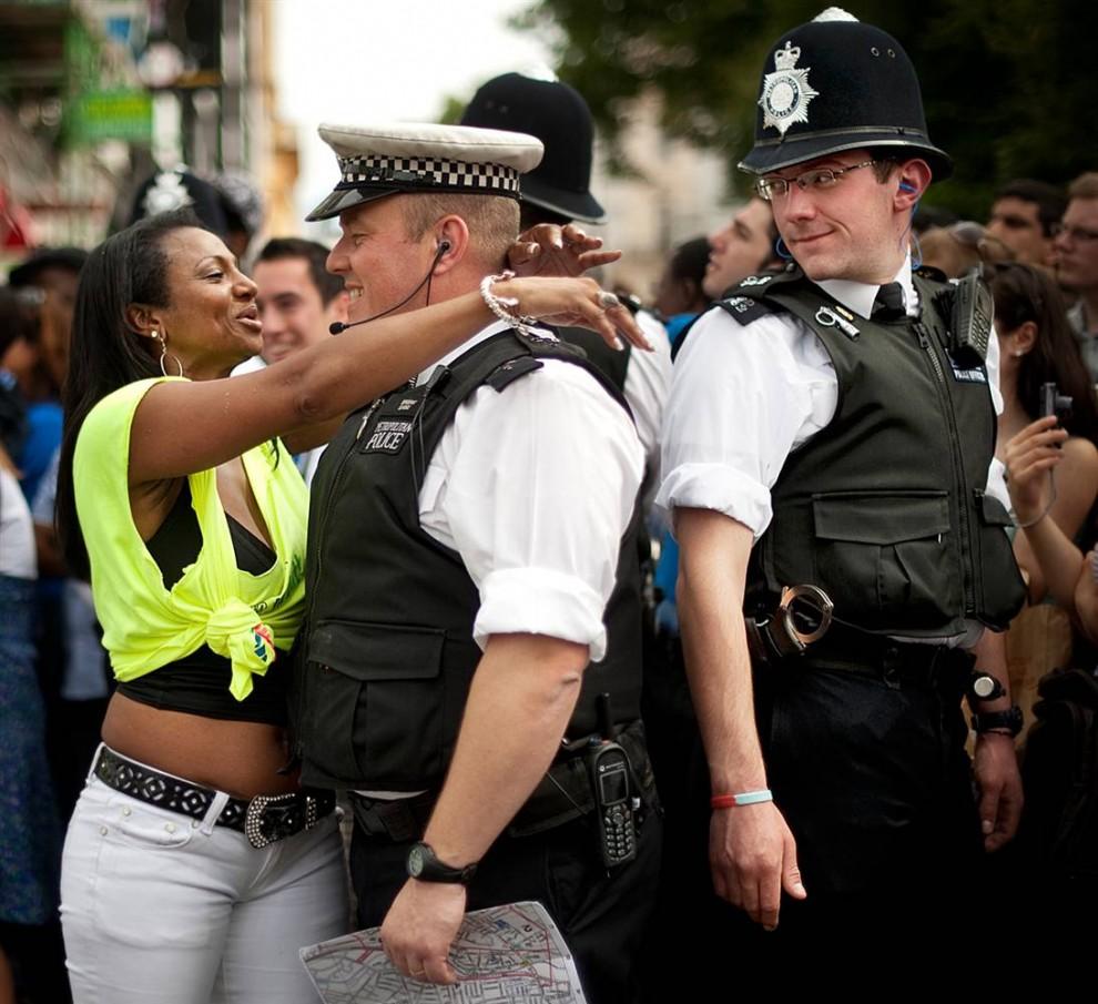 8) Карнавальная танцовщица обнимает лондонского полицейского во время ежегодного Карнавала Ноттинг Хилл 31 августа. Этот карнавал стал крупнейшим уличным праздником карибской культур, в Европе. (Ben Stansall/AFP - Getty Images)