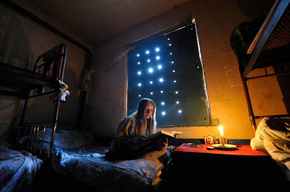 9) Женщина читает в комнате в общежитии Центра реабилитации наркоманов в российском городе Алапаевске 29 августа. Здешние пациенты приходят сюда добровольно и обычно остаются тут в течение целого года. (Konstantin Salomatin/Reuter)