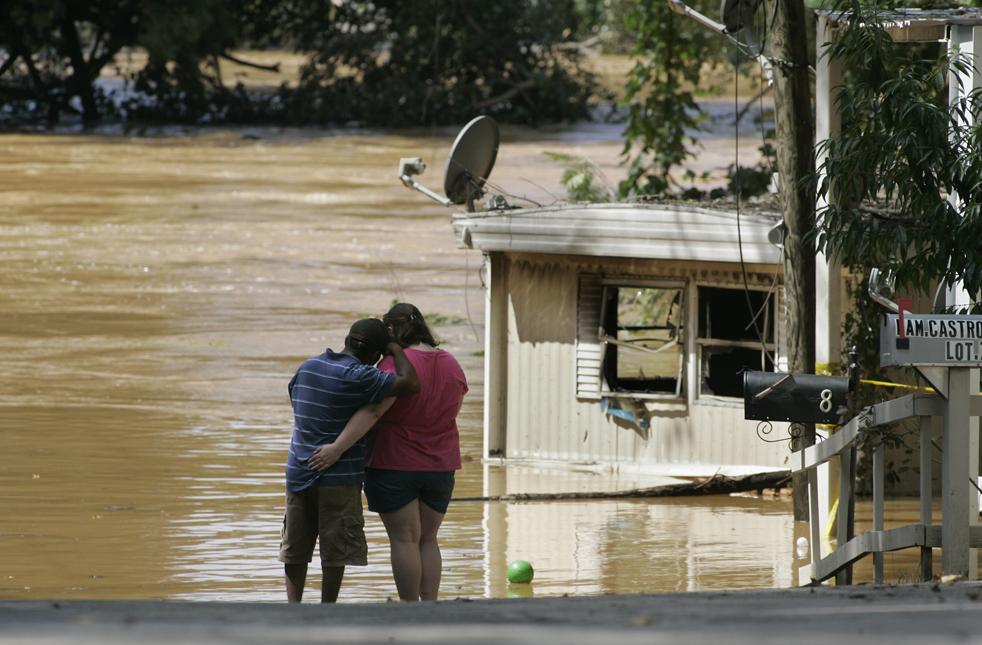 4) 19-летняя Дженнифер Бозман и Набор Торрес стоят на краю бухты Свитвотер, после того, как берега обвалились, и трейлерный парк, в котором они жили, смыло водой. Снимок сделан во вторник, 22 сентября, в городе Остелл, штат Джорджия. (AP/John Amis)