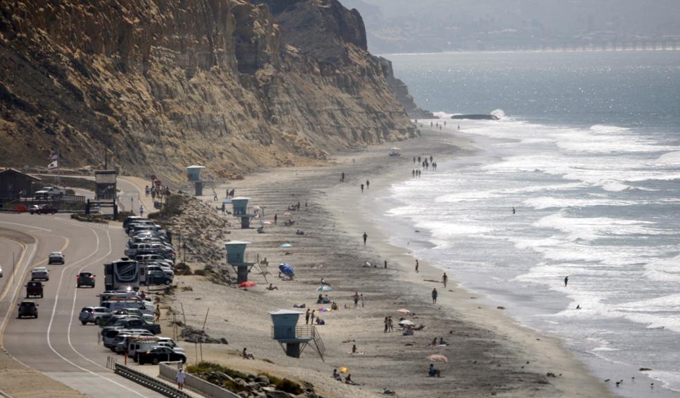 2) Жители южной Калифорнии даже не заметили прихода осени. На снимке, сделанном в понедельник, 21 сентября, в Дель Мар, штат Калифорния, виден ряд автомобилей на хайвее Пасифик Кост у пляжа. Температура на пляже доходила до отметки в 27 градусов. (AP/Lenny Ignelzi)
