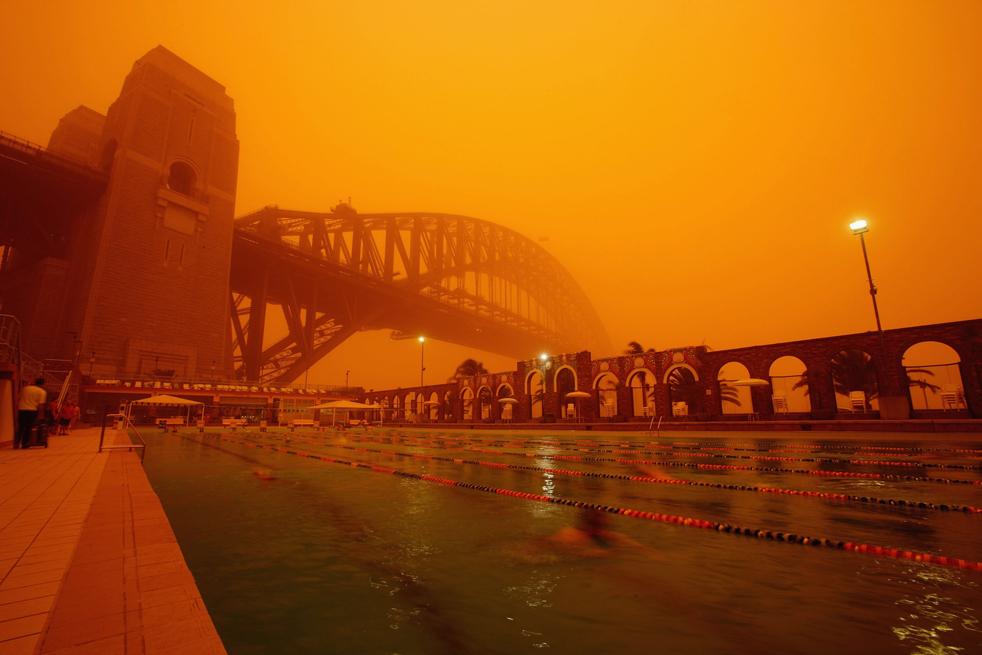 7) Сиднейский мост и Северно-сиднейский олимпийский бассейн 23-го сентября. Сильный штормовой ветер в западной части Нового Южного Уэльса принес огромное облако пыли в Сидней и прилегающие районы. (Getty Images/Brendon Thorne)
