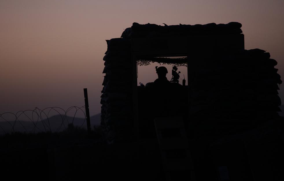 8) Американский морской пехотинец из роты Браво, 1-го батальона 5 морских пехотинцев, наблюдает с поста из мешков с песком на боевой позиции Спин-Гар, в районе Нава. Снимок сделан в провинции Гильменд на юге Афганистана, в четверг, 24 Сентябрь. (AP/Brennan Linsley)