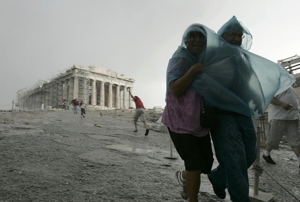 11) Туристы укрываются от внезапной грозы с градом у античного храма Парфенон, спускаясь с холма Акрополя в Афинах в пятницу, 18 сентября. (AP/Petros Giannakouris)