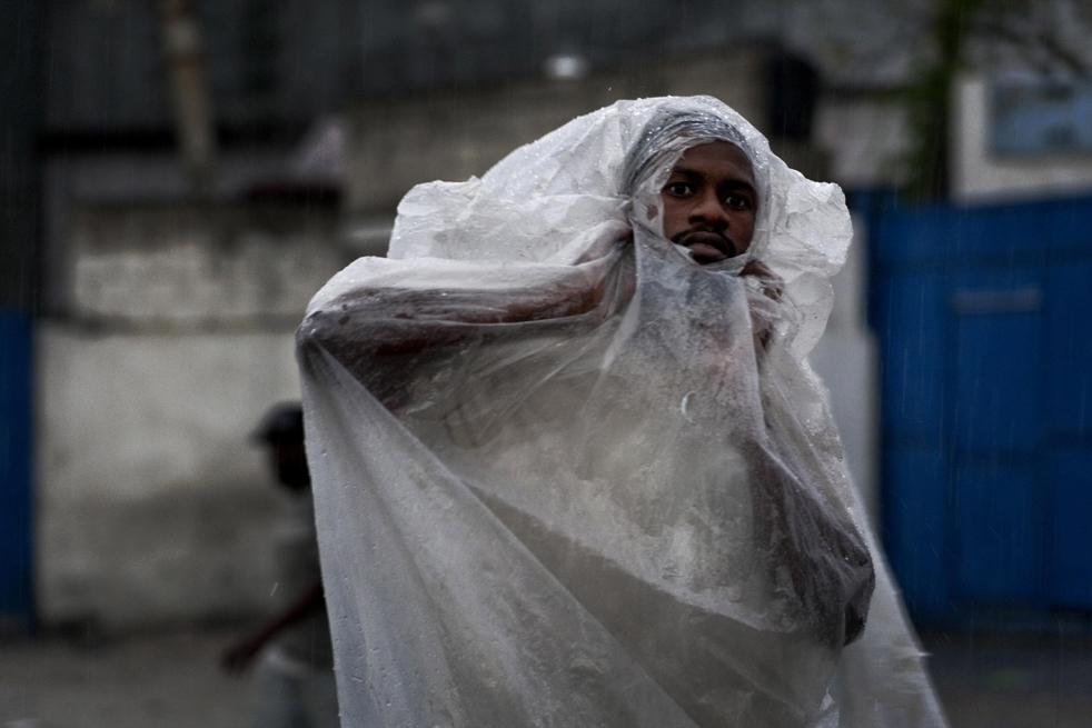 12) Мужчина, выглядывая из целлофана,   идет под дождем в Порт-о-Пренс, во вторник, 22 сентября. (AP/Ramon Espinosa)