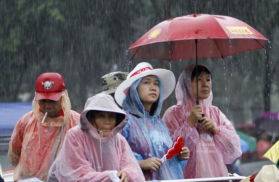 13) Сторонники изгнанного премьер-министр Таиланда Таксина Чинават собрались под дождем у Royal Plaza в Бангкоке в субботу, 19 сентября. Более 6 тысяч полицейских прибыли в субботу в столицу Таиланда для разгона антиправительственной демонстрации, которая собралась в день третьей годовщины военного переворота. (AP/Sakchai Lalit)