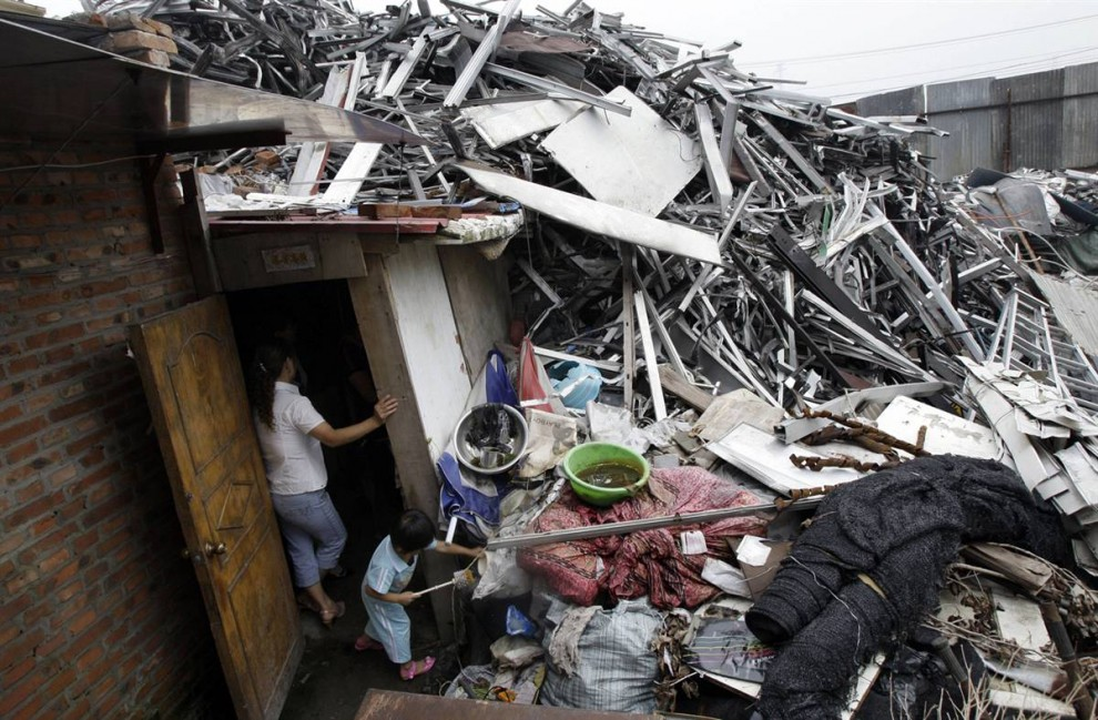 1. Женщина с дочкой стоят в проеме двери заваленного мусором дома в ожидании уборочного автомобиля в центре Пекина. Мусор накапливается в Китае повсеместно, создавая проблемы с санитарией, а все из-за стремительного скачка страны от бедности к богатству. «Если правительство не примет меры, чтобы решить наши проблемы с мусором, Китай может столкнуться с санитарным кризисом в следующие 10 лет», - предупреждает Лиу Яншэн, эксперт управления ликвидацией отходов в университете Пекинг. (Greg Baker / AP)