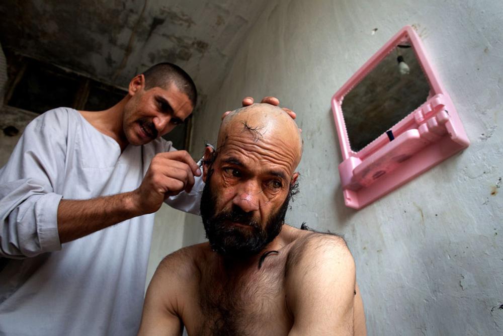 1) Наркоману Ганамгулу бреют голову во время его первого дня  программы детоксикации в кабульском центре реабилитации наркоманов 27 сентября. Ганамгул употреблял наркотики 17 лет. (Paula Bronstein/Getty Images)