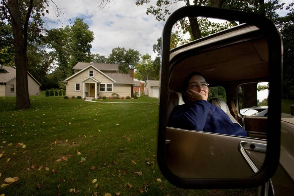 1. Среди лиц, выселенных из домов, которые были отчуждены банками, - Карла Фаннел из Элкхарта, штат Индиана. «Я скучаю по этому дому, действительно скучаю по той жизни, которая была у меня», - говорит она. На этом снимке, сделанном 25 сентября, Фаннел смотрит на дом, который называла своим на протяжении 18 лет. После того, как ее уволили, а последние сбережения кончились, она лишилась права на дом в 2007 году.  Проведя 30 лет в торговле жилыми автофургонами, 52-летняя Фаннел теперь работает на полставки в доставке пиццы и живет в автомобильном фургоне с сыном и дочерью в доме своего зятя. Оглядываясь назад, Фаннел говорит, что могла бы взять ссуду у родственников, если бы раньше призналась в своих проблемах. Она советует: «Не бойтесь просить помощи как можно раньше. Не стесняйтесь». (James Cheng/msnbc.com)