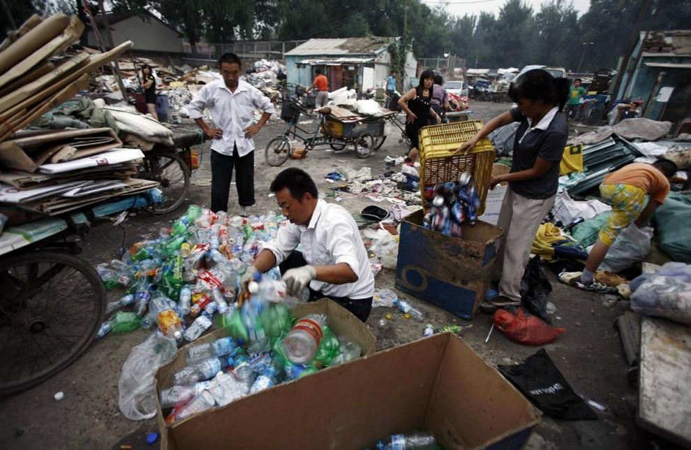 2. Рабочие сортируют мусор в центре переработки в Пекине. За последние двадцать лет объем мусора в Китае увеличился в три раза, достигнув 300 миллионов тонн в год, согласно Не Юнфэн, эксперту по переработке мусора в Пекинском университете Цынхуа. Американцы по-прежнему намного опередили Китай в плане ликвидации мусора, но для Китая эта проблема представляет собой крутой поворот с того времени, когда семьи – тогда, в основном, сельские и бедные – использовали все по нескольку раз. «Раньше с мусором не было проблем, потому что у нас не было супермаркетов, пакетов и бесконечной череды товаров, - говорит Не. – И вдруг правительство запаниковало из-за гор мусора, заполонившего все вокруг». (Greg Baker / AP)