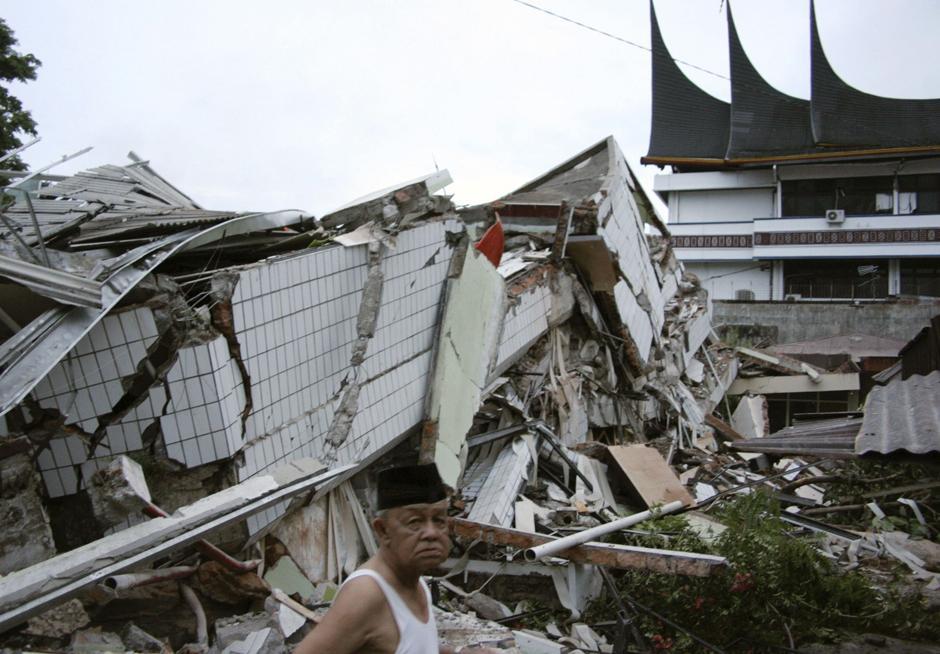 3) Человек стоит перед рухнувшим зданием после землетрясения в Паданге, на острове Суматра в Индонезии.