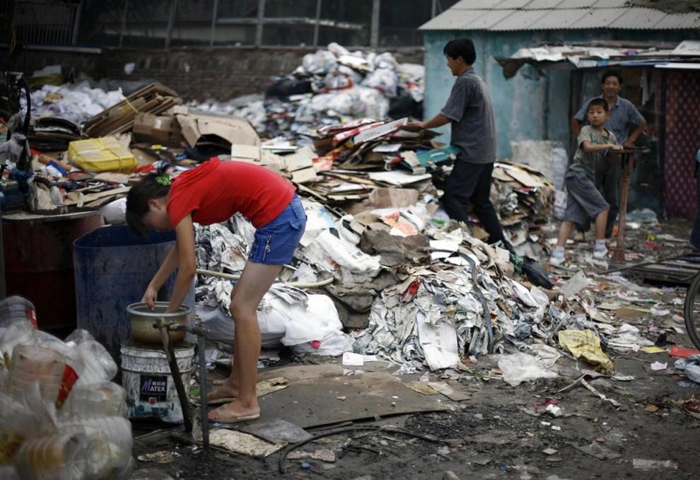 3. Девушка промывает рис в кастрюле у пункта приема утильсырья в Пекине. Протесты в китайских городах приводят к накоплению мусора в деревнях и пригородах. В прошлом году жители Пекина столпились у Министерства охраны окружающей среды, протестуя против неприятного запаха от свалки и требуя поставить там мусоросжигательную печь. В июле был набросан план печи, и свалка закрылась на 4 года раньше. В восточном Пекине власти вложили миллионы долларов на создание свалки и мусоросжигательной печи, которые соответствовали бы гигиеническим нормам. Это случилось только после того, как 200 000 человек подписали петицию против неприятного запаха. (Greg Baker / AP)
