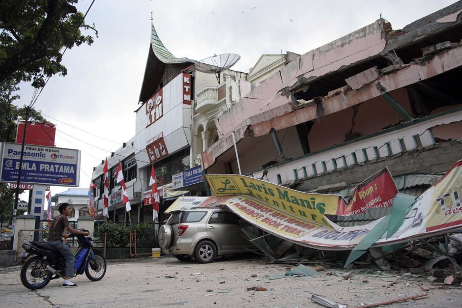 4) Человек садится на мотоцикл у рухнувшего торгового центра после землетрясения в Паданге, на острове Суматра в Индонезии.