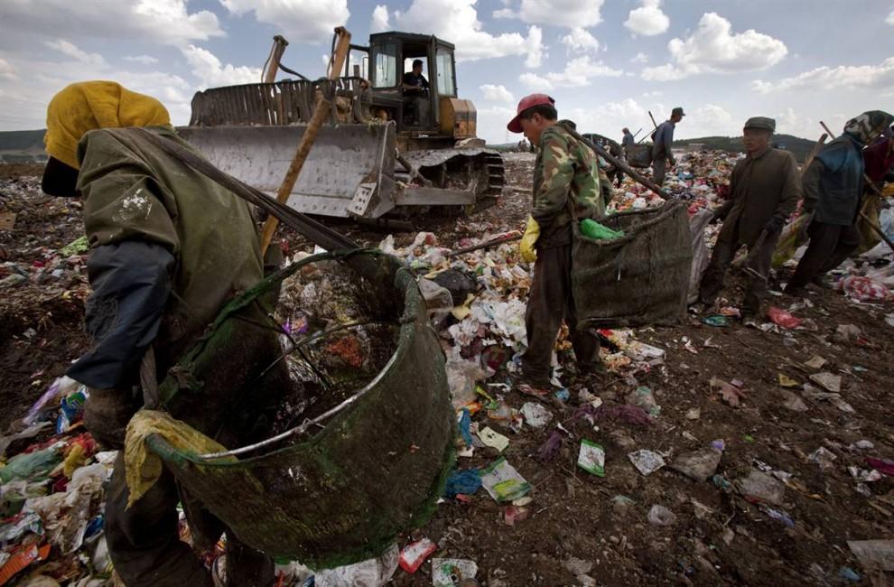 4. Рабочие просматривают мусор в Чанчуне, северо-восточный Китай. По меньшей мере, 85% всего мусора Китая (который составляет примерно 7 миллионов тонн) находится на свалках, большинство – на не лицензированных мусорках в пригородах. На некоторых свалена лишь пластмасса и стекловолокно. Дожди выносят тяжелые металлы, аммиак и бактерии в подземные воды и почву, а пары разложения выделяют в воздух метан и углекислый газ. (AP)