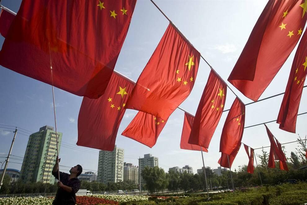 5) Человек разворачивает китайский национальный флаг в понедельник, 28 сентября в парке Пекина, где была установлена целая серия знамен перед празднованием 60-й годовщины КНР. (Alexander F. Yuan/AP)