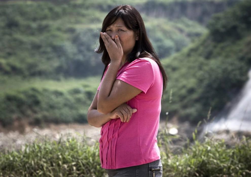 5. Жительница поселка смотрит на огромную свалку недалеко от городка Чжанлидун, запах которого чувствуется задолго до того, как она появляется на горизонте. Менее чем за пять лет свалка в Чжэнчжоу превысила по объемам поселок в 1000 человек. Персики и вишни на деревьях погибают под нашествием насекомых, привлеченных смрадом свалки. Поля не обработаны и загрязнены токсическими отходами. Каждый день около 100 тонн мусора прибывает из Чжэнчжоу – столицы провинции с 8 миллионами жителей. (Andy Wong / AP)