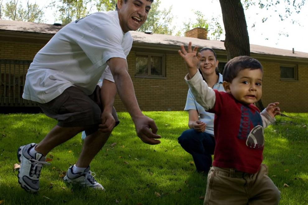 5. Роберто и Патришиа Негрет играют со своим годовалым сыном Роберто младшим на заднем дворе их дома 17 сентября.  38-летний Роберто хочет уйти из дома, так как не может платить ипотеку. Он потерял работу и 10 месяцев был безработным, но потом вернулся на свое рабочее место, но зарплату ему урезали. «Я не зарабатываю столько, сколько зарабатывал раньше», - говорит он.  «Я знаю, что не справлюсь с ипотекой», - говорит он. Они переедут в квартиру, как только его ипотекодержатель решит его права на имущество. (James Cheng/msnbc.com)