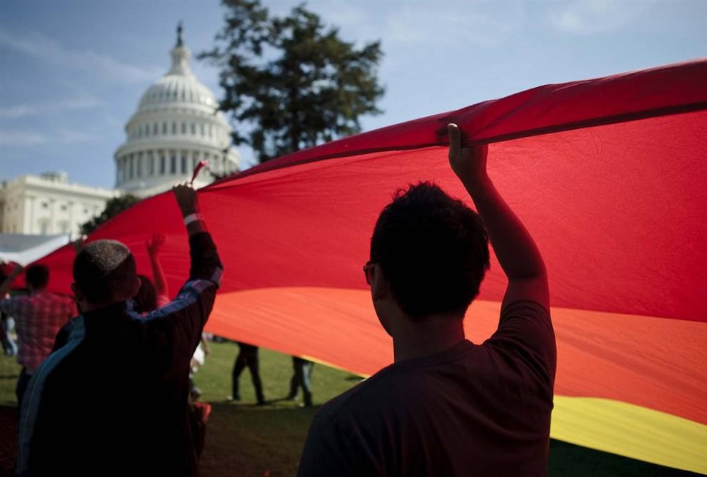 5) Активисты несут Радужный флаг на лужайке Капитолия. Активисты собрались, чтобы добиться от администрации Барака Обамы и Конгресса США, выполнения обещаний по продвижению гражданских прав лесбиянок, геев, бисексуалов и транссексуалов. (Brendan Smialowski/Getty Images)